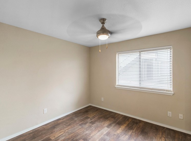 Bedroom with hardwood style flooring, ceiling fan, and window with blinds