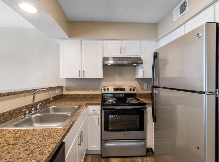Fully equipped kitchen with brushed nickle appliances, white cabinets, and marble styled counter tops