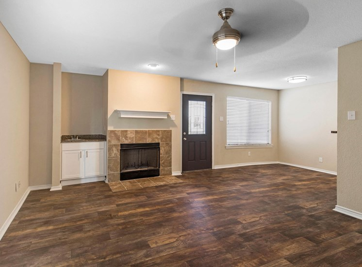 Living room with ceiling fan, fireplace, and hardwood style flooring