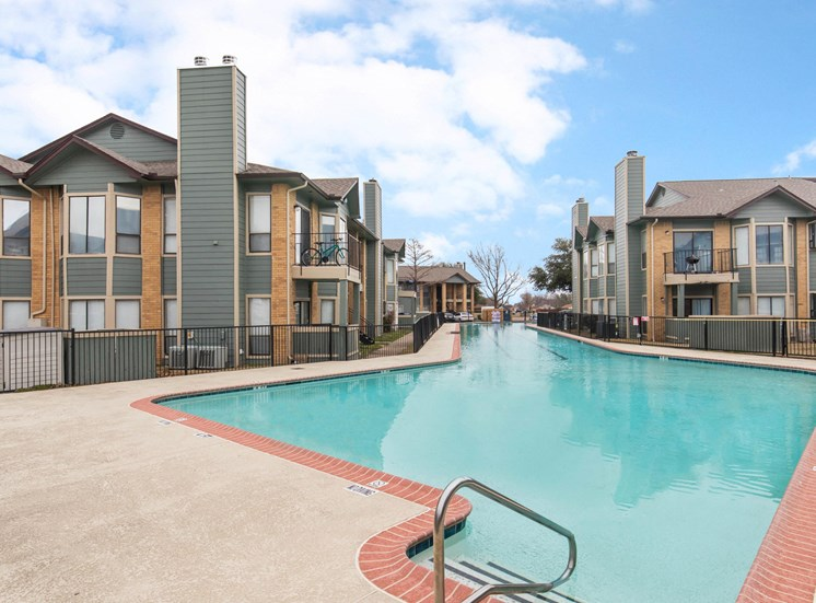 Swimming pool with tanning deck, blue skies and white clouds up above, and apartment building exterior in the background