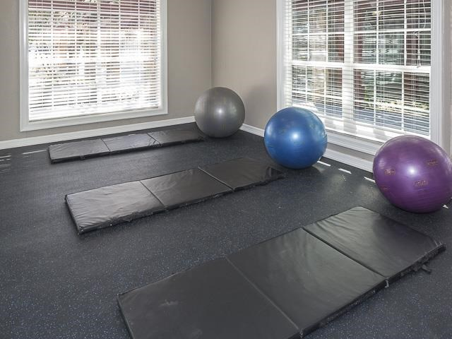 Fitness center with black fitness mats on the floor, and workout equipment in the background