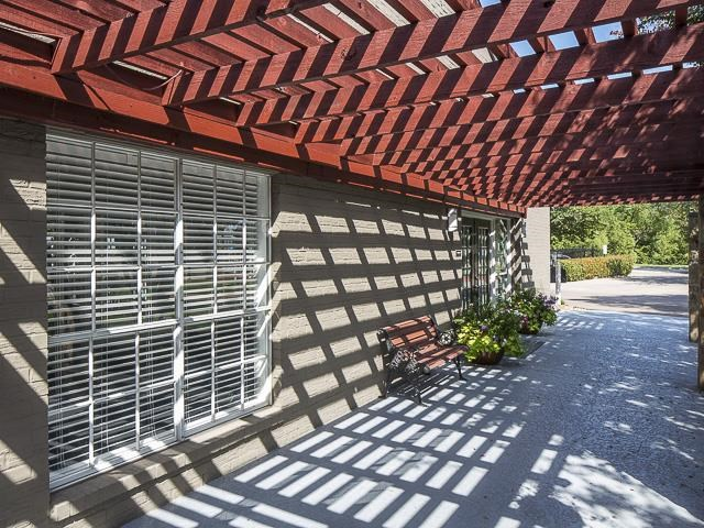 Wooden pergola with bench, plans, and windows with blinds