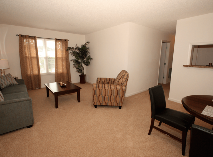 Spacious living room with carpet flooring, couch, coffee table, chair, dining room table with chairs, and large mirror with curtains