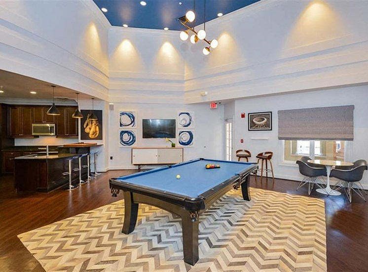 Clubhouse Lounge Area with Vaulted Blue Ceiling Above Billiards Table on Area Rug