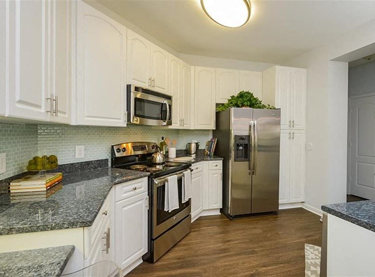 Model Kitchen with Grey Counters White Cabinets and Stainless Steel Appliances