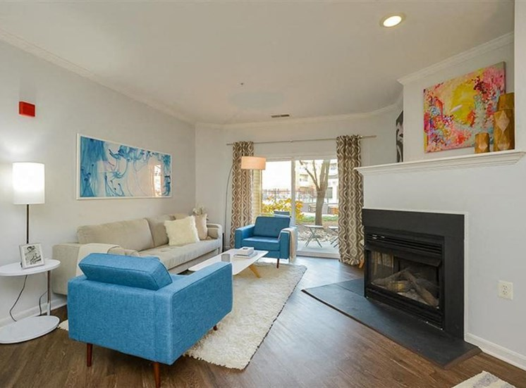 Model Apartment with Living Room with Fireplace Grey Couch Blue Armchairs and Sliding Glass Patio Door