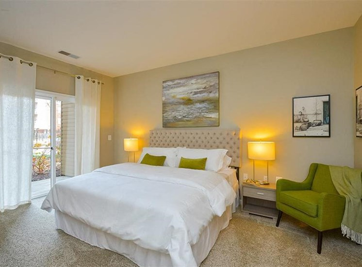 Model Bedroom with Bed Under Art with Sliding Glass Door on One Side and Green Armchair on the Other