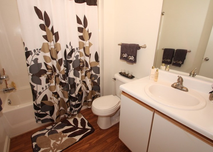 Bathroom with decorated shower curtain, towel bar above toilet, and hardwood style flooring