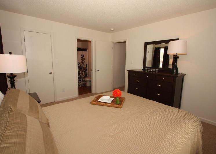 Decorated bedroom with large wooden dresser and tan and brown color scheme