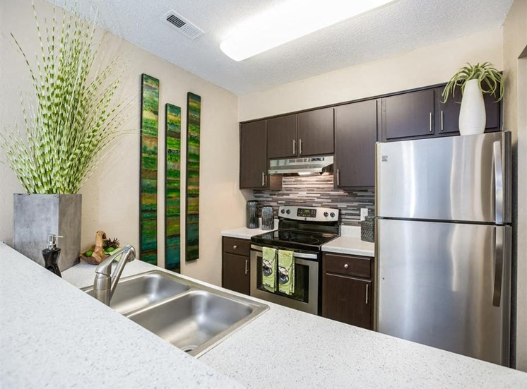 Model Kitchen with Brown Cabinets Stainless Steel Appliances Grey Counters with Glass Backsplash and Green Decorations