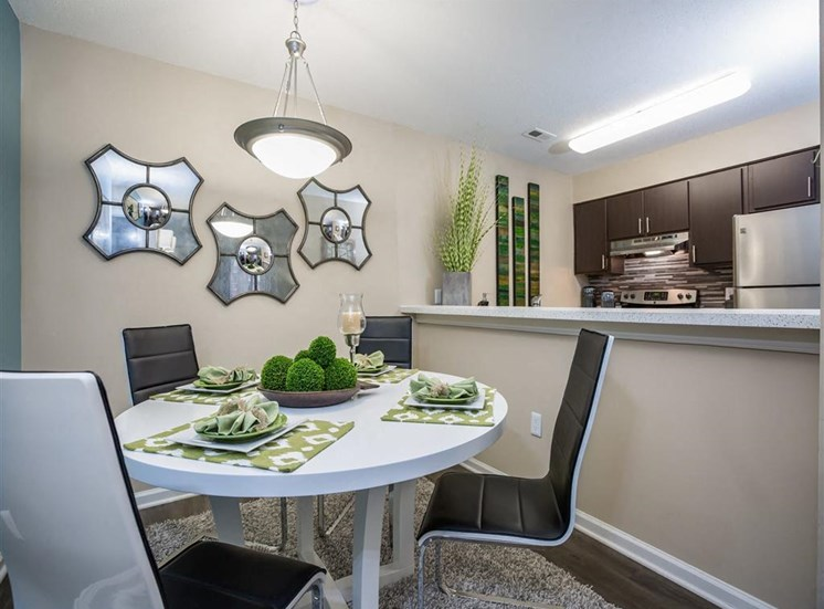Dining Room with White Table with Placemats and Decorations Next to Open Kitchen with Stainless Steel Appliances and Brown Cabinets