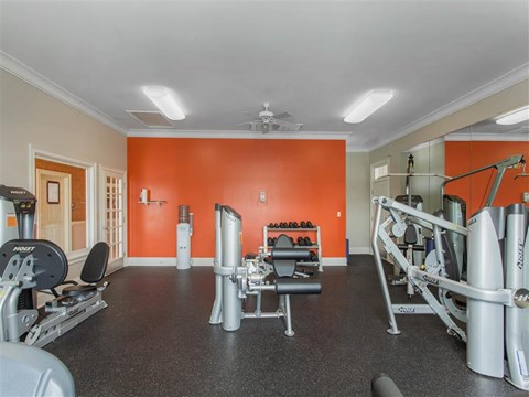 Fitness Center with Exercise Equipment with Orange and Mirror Accent Wall
