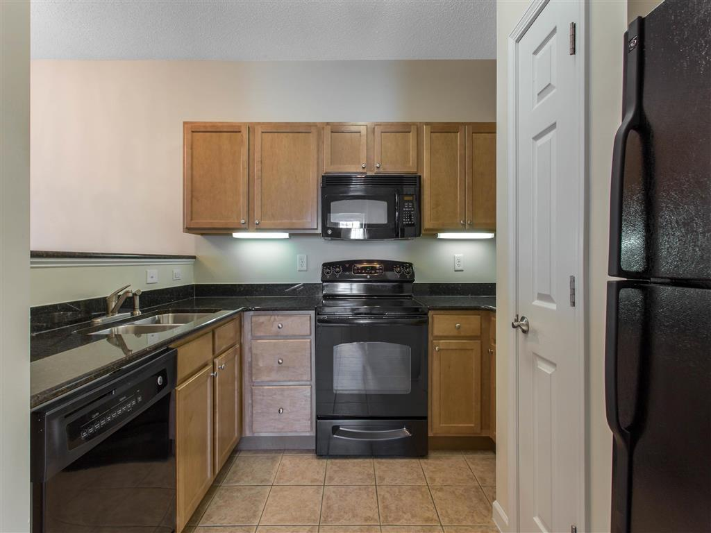 Kitchen with Brown Cabinets Black Appliances and Black Counters Pantry Closet and Breakfast Bar