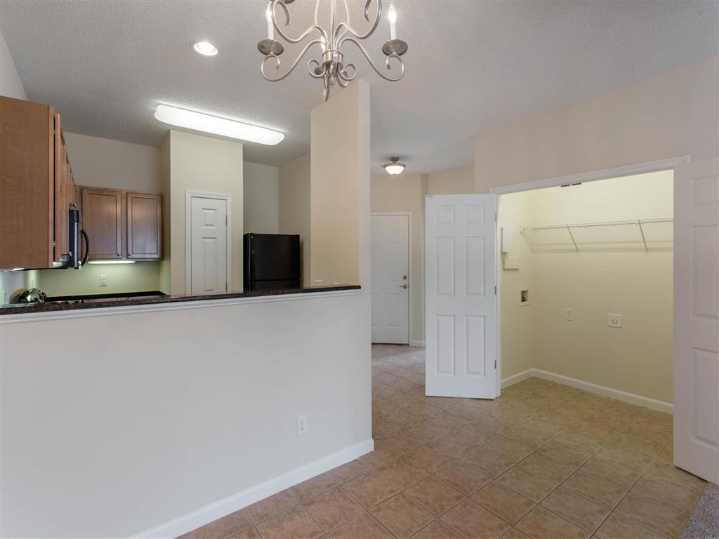 Open Floor Plan View From Carpeted Living Room with Breakfast Bar Brown Kitchen Cabinets and Utility Closet