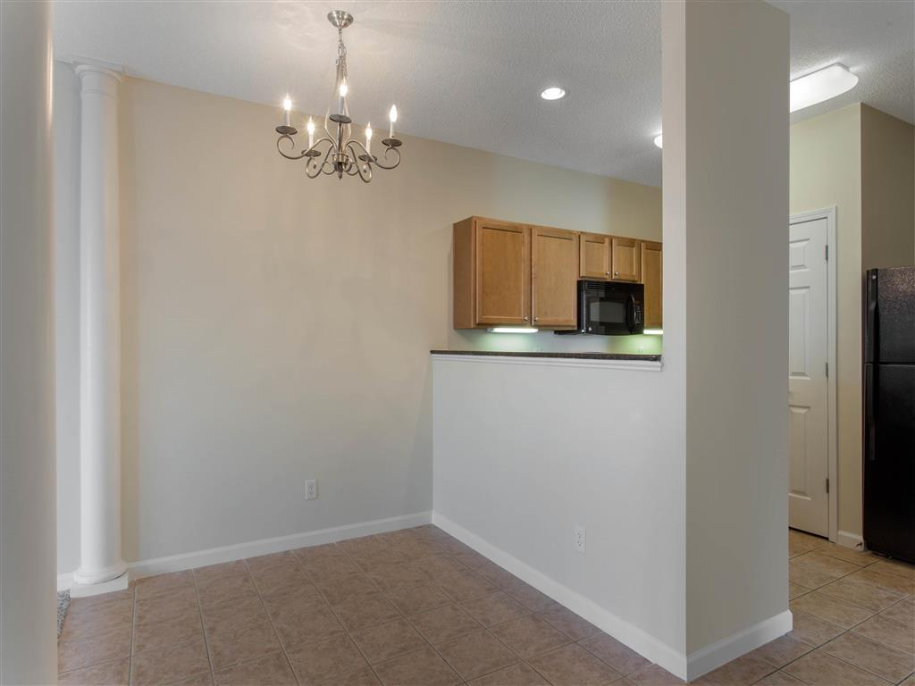 Open Floor Plan View From Carpeted Living Room with Breakfast Bar Brown Kitchen Cabinets