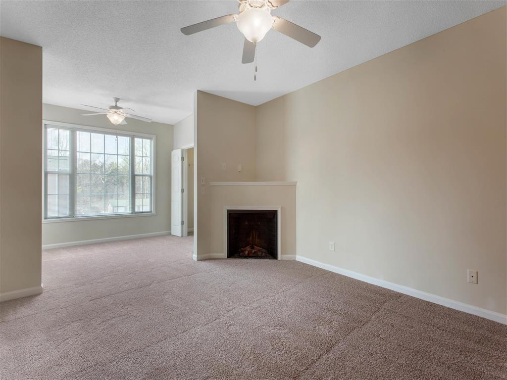 Open Floor Plan View From Carpeted Living Room with Breakfast Bar Brown Kitchen Cabinets and Fireplace