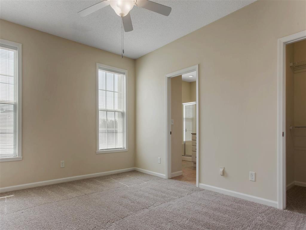 Carpeted Bedroom with En-Suite Bathroom Ceiling Fan and Window