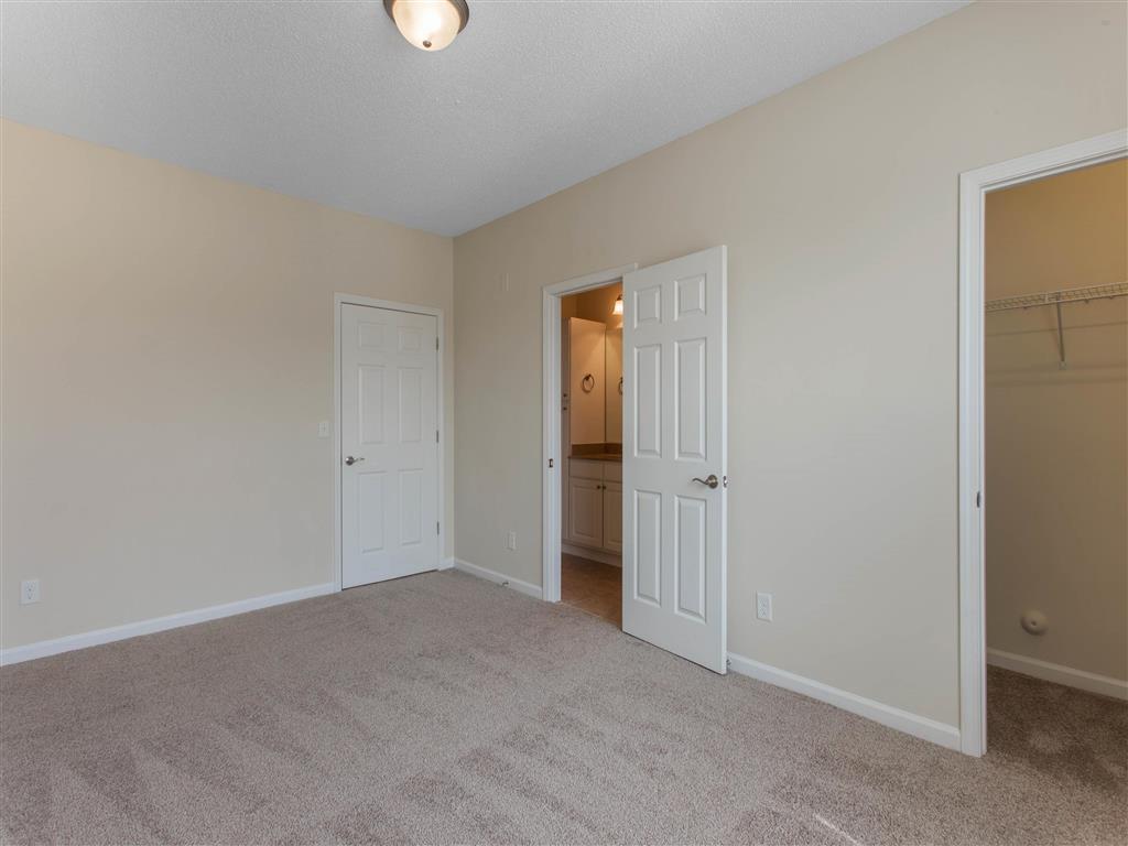 Carpeted Bedroom with En-Suite Bathroom and Walk-in  Closet
