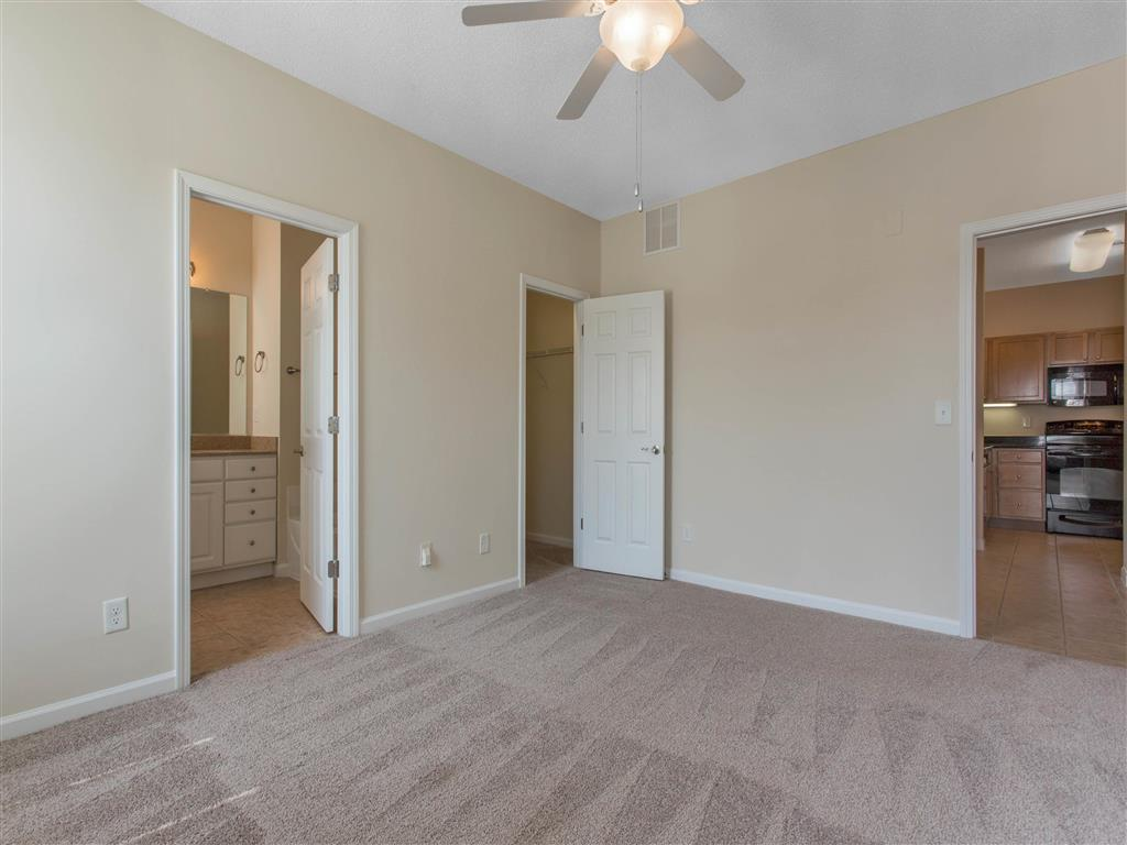 Carpeted Bedroom with En-Suite Bathroom Ceiling Fan and Kitchen Visible Through Bedroom Door