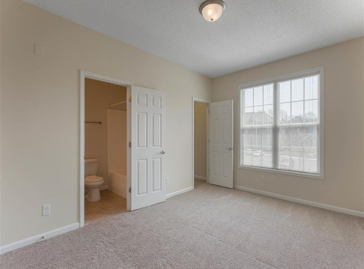 Carpeted Bedroom with Large Window En-Suite Bathroom and Walk-in Closet
