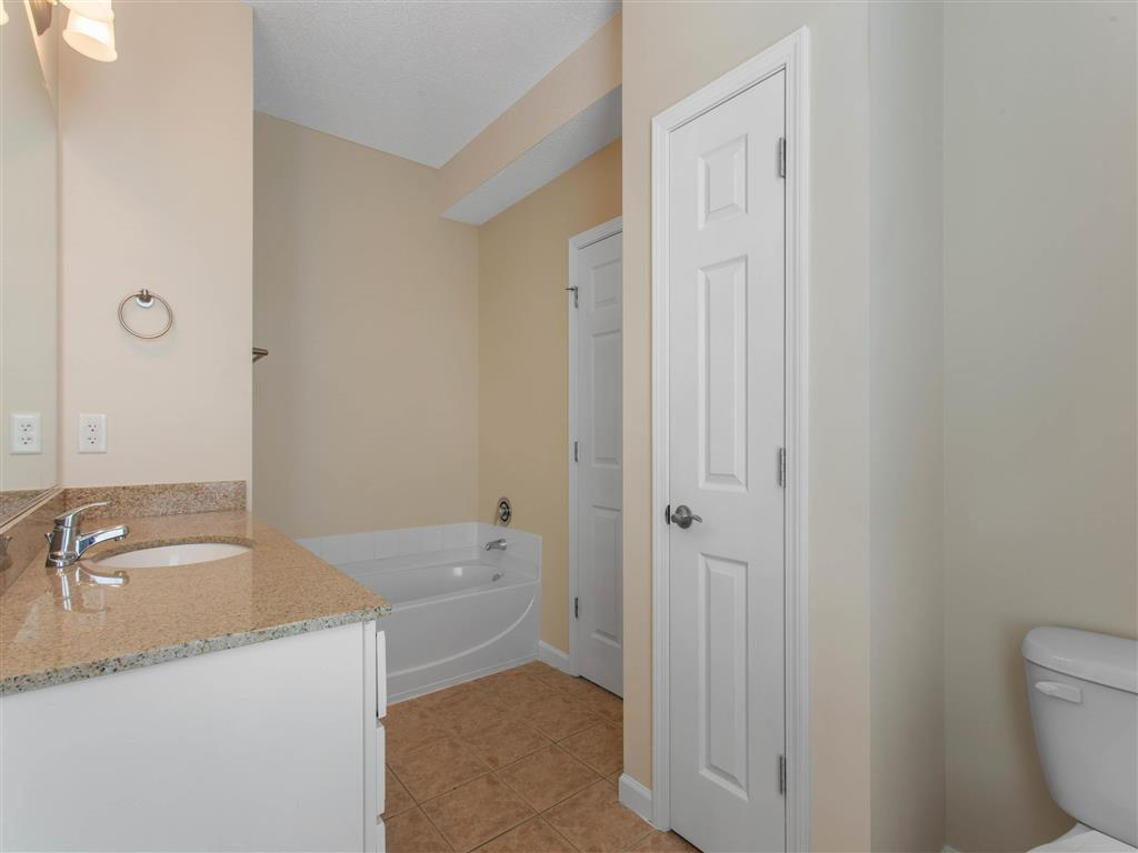 Bathroom with Bathtub Tan Counters White Cabinets and Linen Closet Door