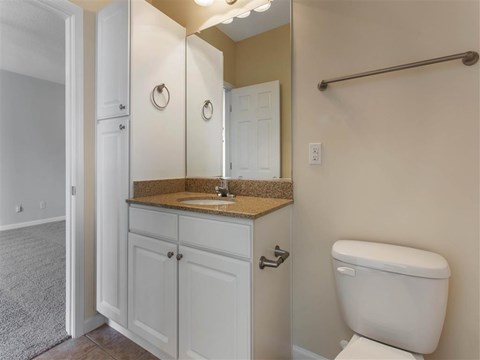 Bathroom with Tan Counters White Cabinets and Linen Closet