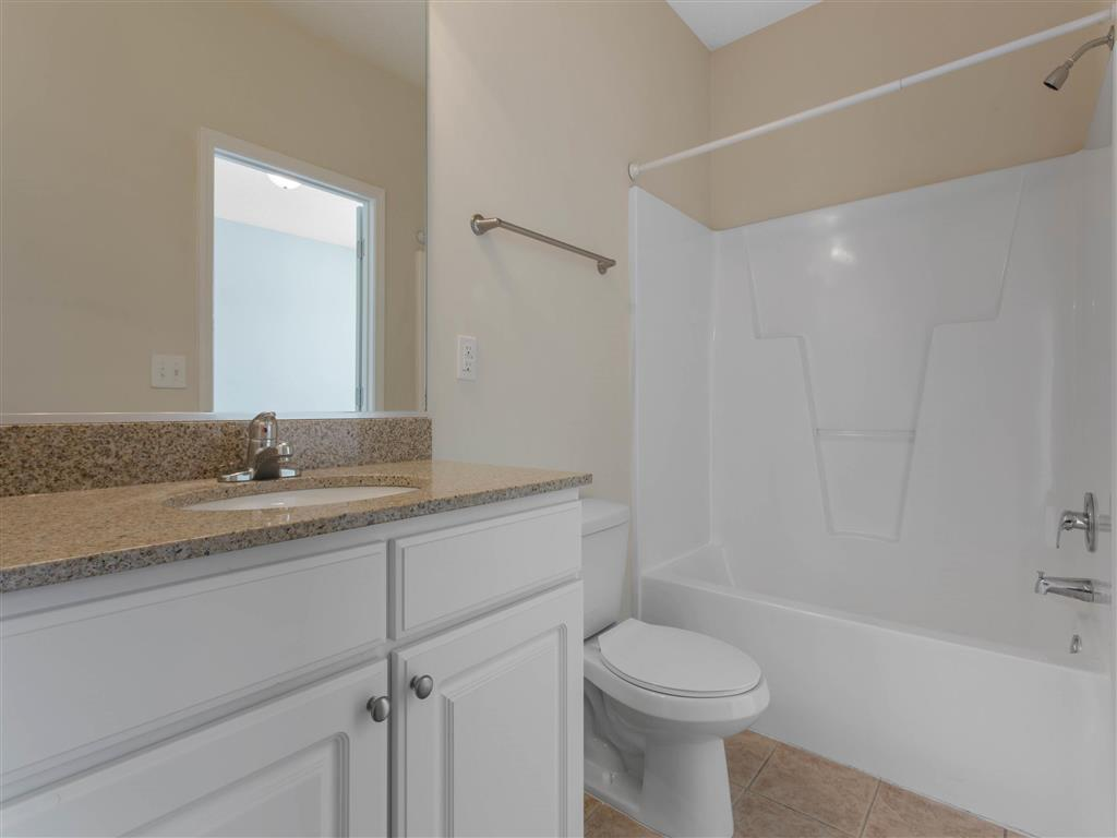 Bathroom with Bathtub and Shower Tan Counters White Cabinets and Linen Closet Door