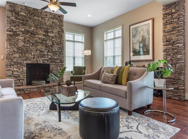 Clubhouse Seating Area with Grey Couches Triangle Glass Coffee Table Brick Fireplace with Windows and Decorations
