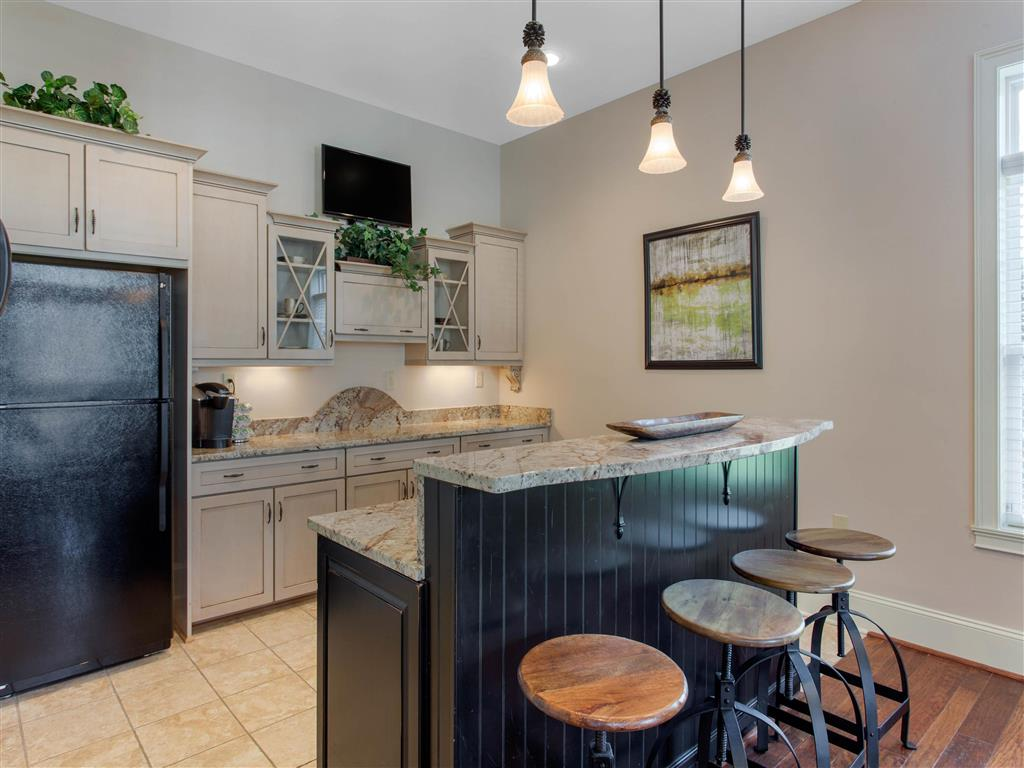 Clubhouse Kitchen with Tan Counters Black Appliances and Wood and Metal Stools at Breakfast Bar