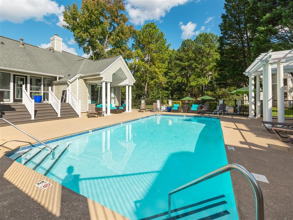 Leasing Office Exterior with Swimming Pool and Sun Deck with Lounge Chairs and Pergola  with Trees and Building Exteriors in the Background