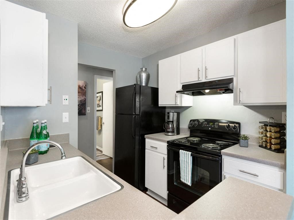 Decorated Kitchen with White Cabinets Grey Counters Double Sink and Black Appliances