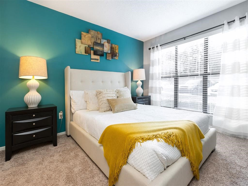 Model Bedroom With Large Windows and Blue Accent Wall White Bed Frame with Decorative Pillows  and Yellow Throw Blanket Across the Corner Two Black Night Stands with White Lamps
