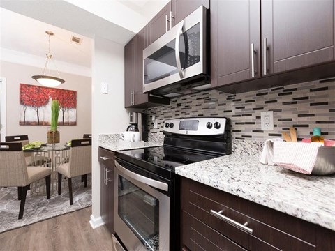 Model Kitchen  with Brown Cabinets Glass Backsplash and Stainless Steel Appliances