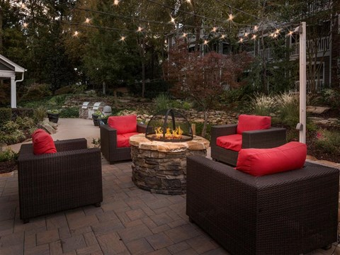 Outdoor Fire Pit Surrounded By Patio Arm Chairs with Red Cushions