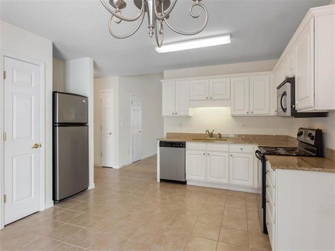 Kitchen with White Cabinets Brown Counters and Stainless Steel Appliances
