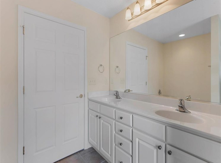 Bathroom with White Cabinets White Counters and Closet Door