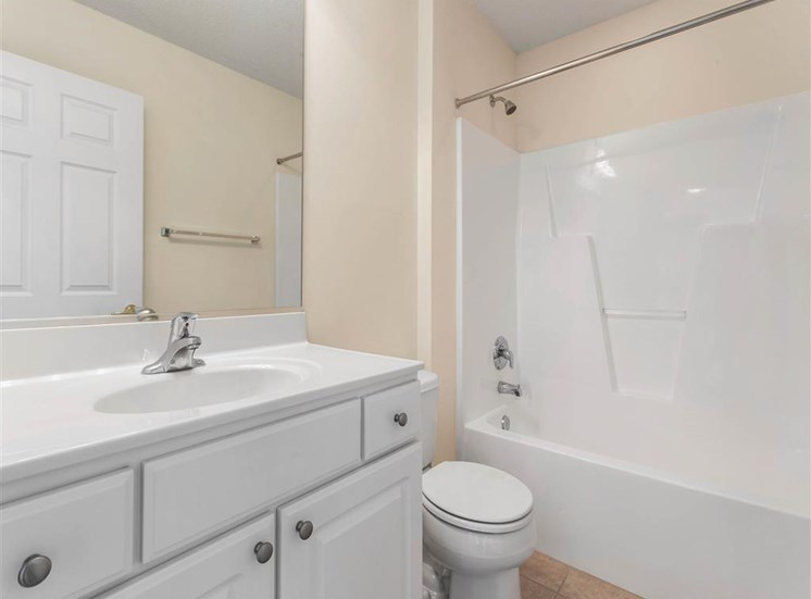 Bathroom with White Cabinets White Counters and White Bathtub and Shower