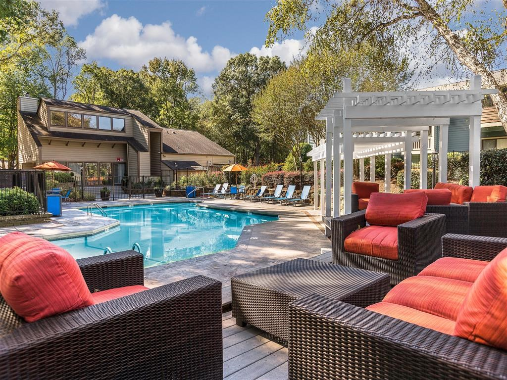 Swimming Pool with Poolside Lounge and Pergola with Leasing Office Exterior in the Background
