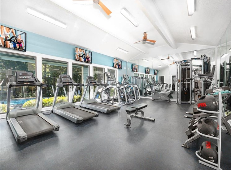 Fitness Center with Exercise Equipment in Front of WIndow  with Mounted TV