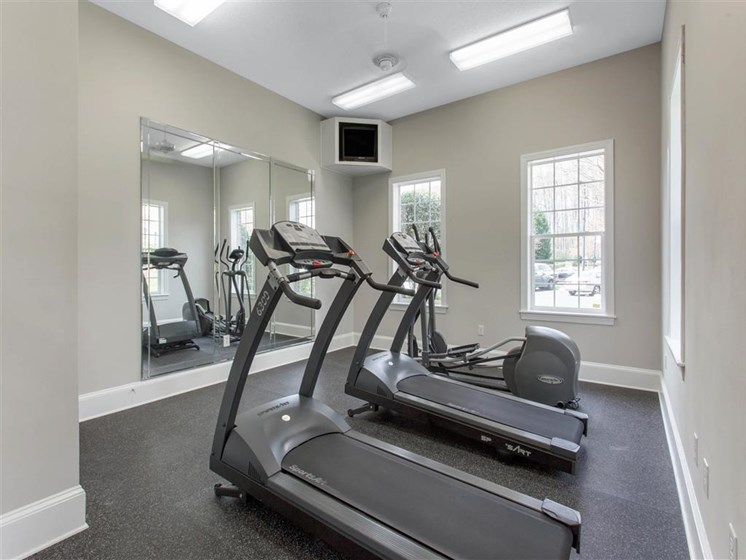 Fitness Center with Exercise Equipment  Mirror Accent Wall and Mounted TV