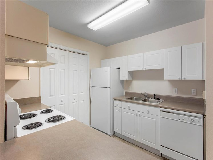 Kitchen with White Cabinets and Appliances with Beige Counters and Utility Closet