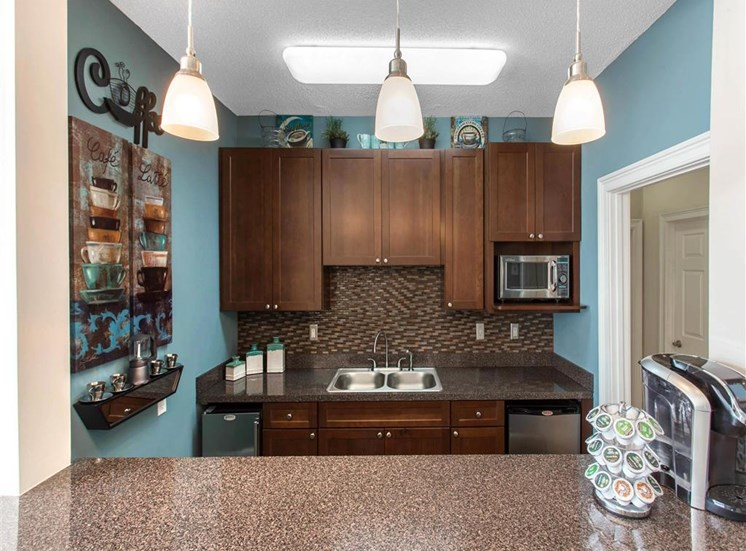 Clubhouse Kitchen with Breakfast Bar Brown Cabinets and Stainless Steel Appliances