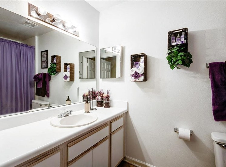 Decorated Bathroom with Vanity White Counters and White Cabinets with Wood Accents  Purple Shower Curtain in Mirror Reflection