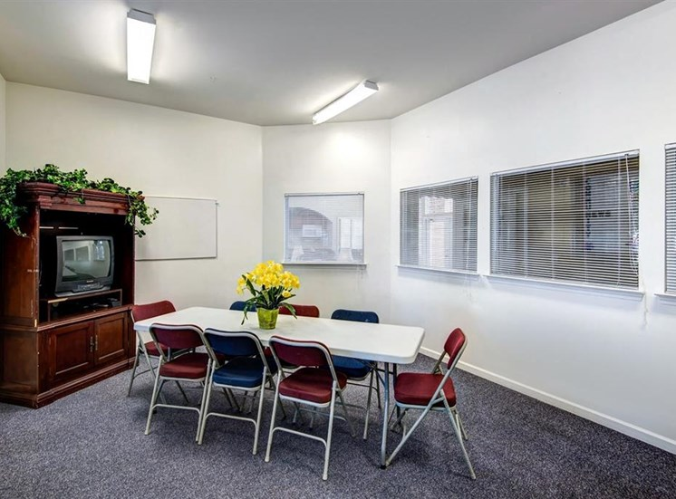 Resident Lounge Room with Large Windows Folding Table and Chairs in Front of a TV in an Entertainment Center