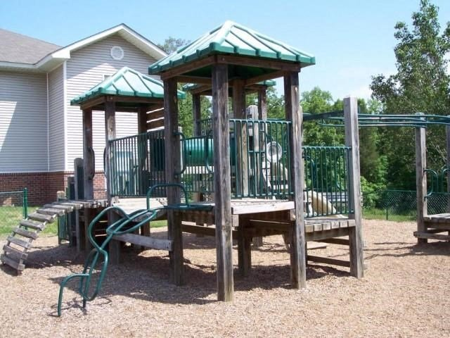 Wooden Playground with Green Accents on Mulch with Building Exterior and Treeline in the Background
