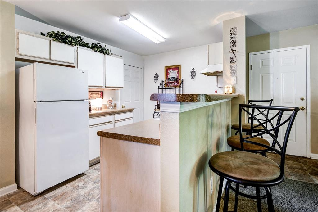 Model Kitchen ith White Cabinets and Appliances and Breakfast Bar and Bar Stools