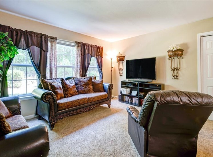Model Living Room with Two Brown Couches and a Recliner as well as A TV on an Entertainment Center
