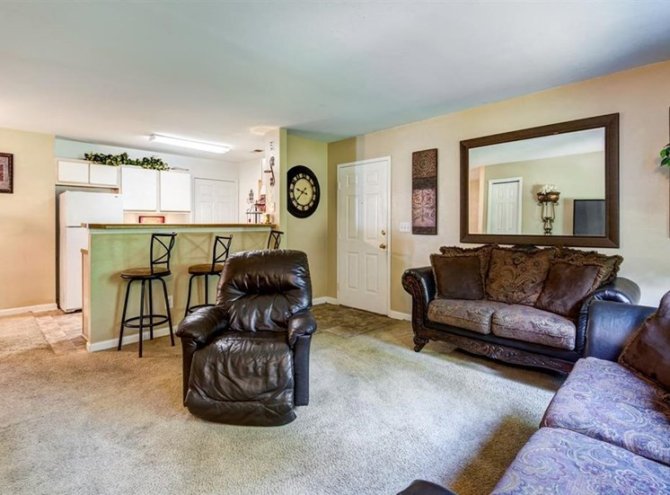 Model Living Room with a Mirror on the Wall Two Brown Couches and a Recliner and Breakfast Bar with Bar Stool and Kitchen in the Background