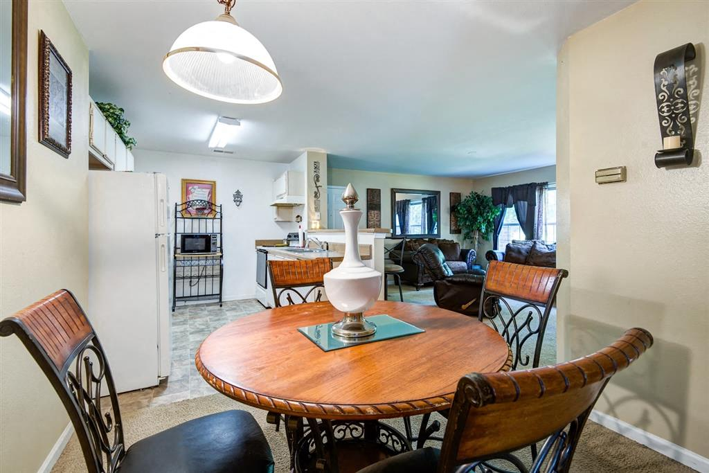 Open Model Floor Plan with Dining Room Table in DIning Room with Kitchen and Ling Room in the Background