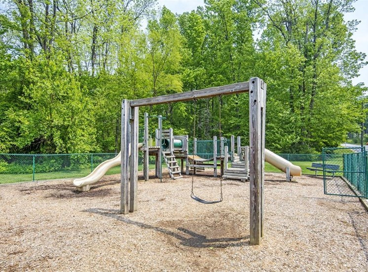 Fenced in Wooden Playground with Swing Set on Mulch